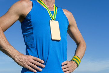 Gold medal in the shape of mobile phone hanging from a green and yellow ribbon on the chest of an athlete against blue sky