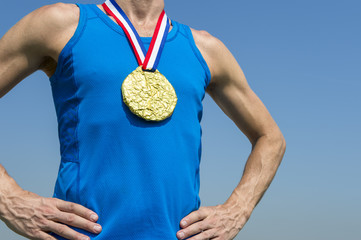Athlete standing with gold medal hanging from a red white and blue ribbon against blue sky