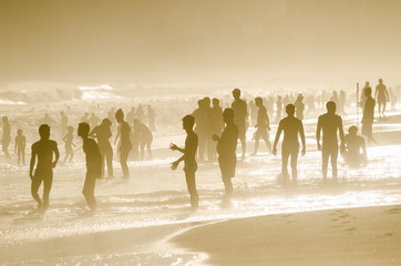 Silhouettes of carioca Brazilians standing on the misty sunset shore of Ipanema Beach in Rio de Janeiro, Brazil