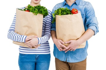 Mid section of couple holding grocery bags