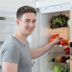 Junger Mann am Kühlschrank voll Gemüse