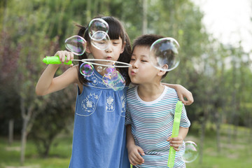 Siblings blowing soap bubble outdoors