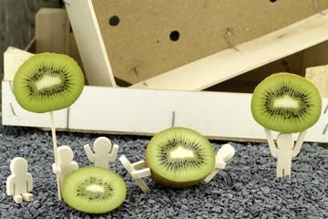 Hölzerne Figuren präsentieren fröhlich Scheiben von Kiwi