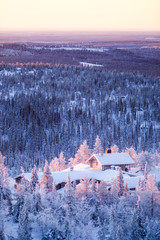 Winter scenery view over a cabin in frozen forest.