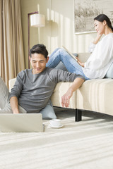 Husband using laptop and wife reading book at home