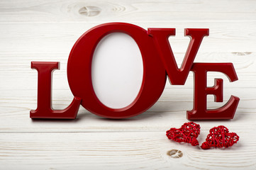 "Red frame for pictures ""love"" on the wooden background."