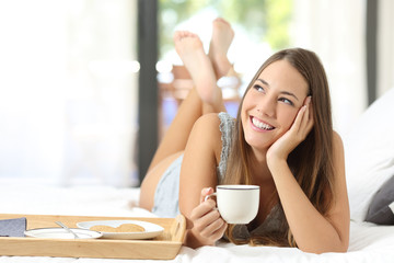 Happy girl having breakfast holding a coffee cup