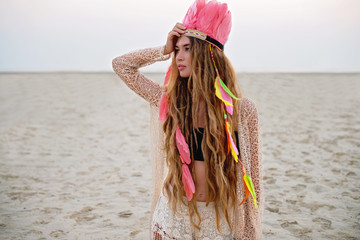 Boho chic beautiful model on the beach in peach colors