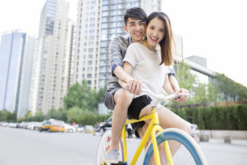 Happy young couple riding bicycle