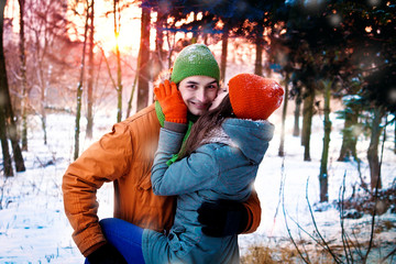 Young couple in love hugging in winter forest