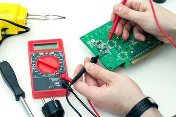 Electrician checks electronic hardware with a multimeter in the