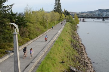 People biking and jogging along the Eastbank Esplanade in Portland, Oregon. Marquam and Hawthorne bridges in background.