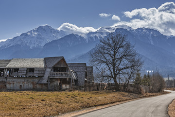 Rural scenery with old abandoned wooden farmhouse in the valley of snowy Bucegi mounains, Brasov county, Romania.