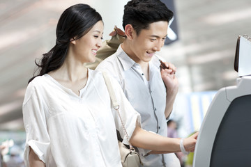 Young couple using ticket machine at the airport