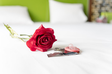 Condom and red rose on bed, Valentine concept