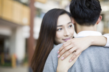 Young couple embracing in shopping mall