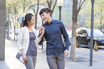 Young couple holding hands walking on sidewalk