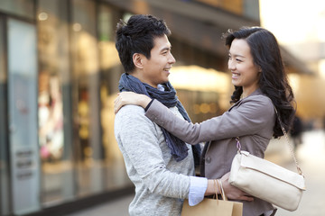 Fashionable young couple arm around each other in city street