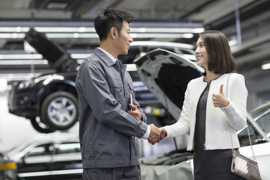 Auto mechanic and car owner shaking hands
