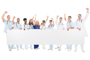 Happy Medical Team With Arms Raised Holding Blank Billboard