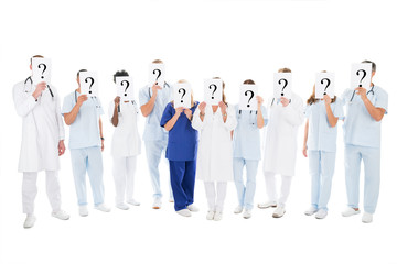 Medical Team Covering Faces With Question Mark Signs