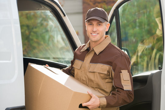 Young Delivery Man Removing Cardboard Box From Truck