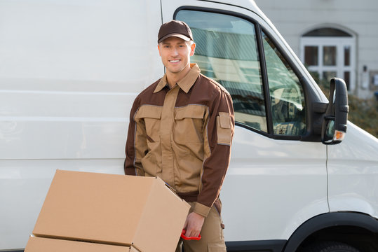 Confident Delivery Man Pushing Parcels On Handtruck