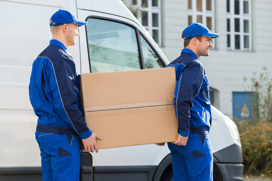 Delivery Men Carrying Cardboard Box By Truck