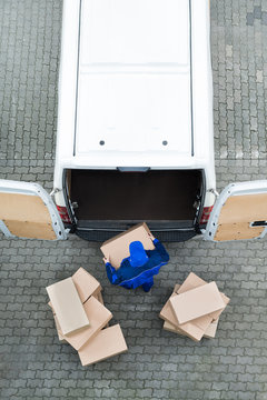 Delivery Man Unloading Cardboard Boxes From Van On Street