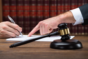 Judge Assisting Client To Sign Legal Document In Courtroom