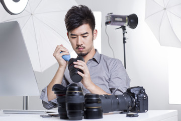 Photographer cleaning camera lens in studio