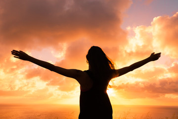 life achievements and success concept.. Sporty girl raising arms towards beautiful glowing sunshine.