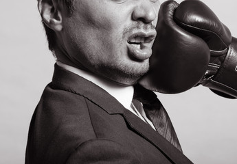 Business man getting punch with boxing glove.
