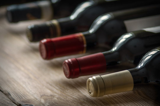 Row of wine bottles on the wooden table. Low depth of field.