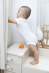 Chinese baby boy playing on a dressing table