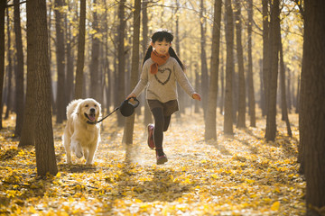 Little girl running with dog in autumn woods