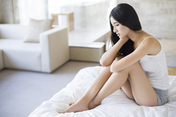 Displeased young woman sitting on bed