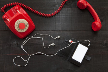 The image shows a hooked off red old retro phone  with a smartphone with white earphones on wooden background