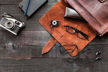 The image shows a retro or hipster bag for man or woman with stuff such as glasses , vintage camera, leather bag and a book note on a wooden background