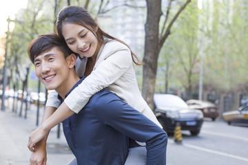 Young man piggybacking girlfriend