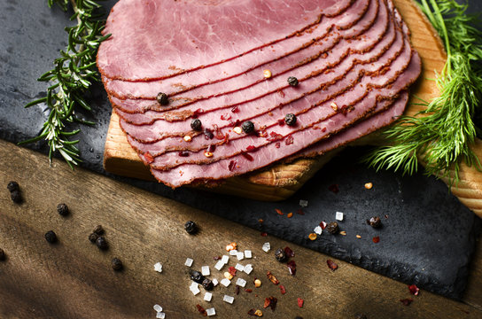 fresh sliced beef pastrami surrounded by herbs in wooden chopping board