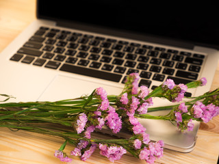 Laptop and flower on wooden desk
