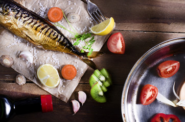 Cooking background. Smoked fish with spices,fruits and lemon on a wooden background.