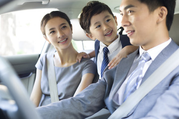 Young couple with son riding in car together