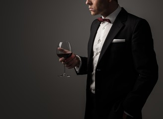 Sharp dressed man wearing jacket and bow tie with glass of vine