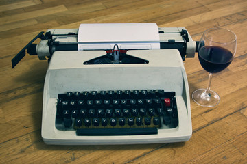 Typewriter with Glass of Wine on Wooden Floor