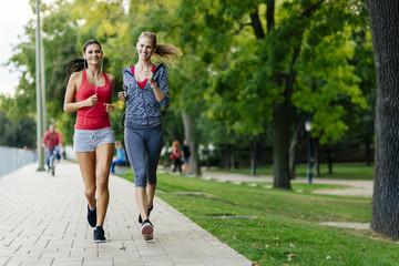 Two women jogging in park - fototapety na wymiar