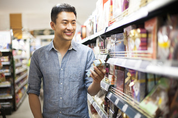 Young man shopping in supermarket