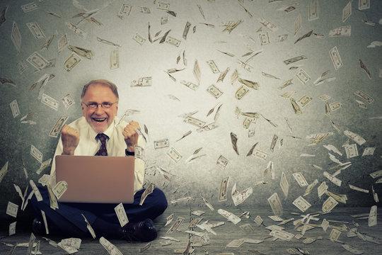 Senior man using laptop building online business making money dollar bills falling down.