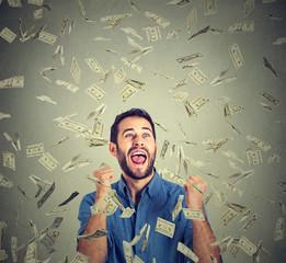 happy man pumping fists celebrates success screaming under money rain